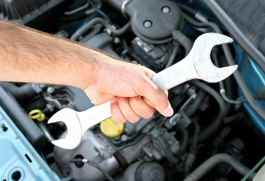 Изображение руки с гаечным ключом на фоне автомобиля